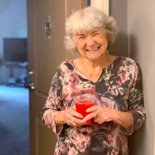 Resident standing in her doorway smiling at Oxford Villa Active Senior Apartments in Wichita, Kansas