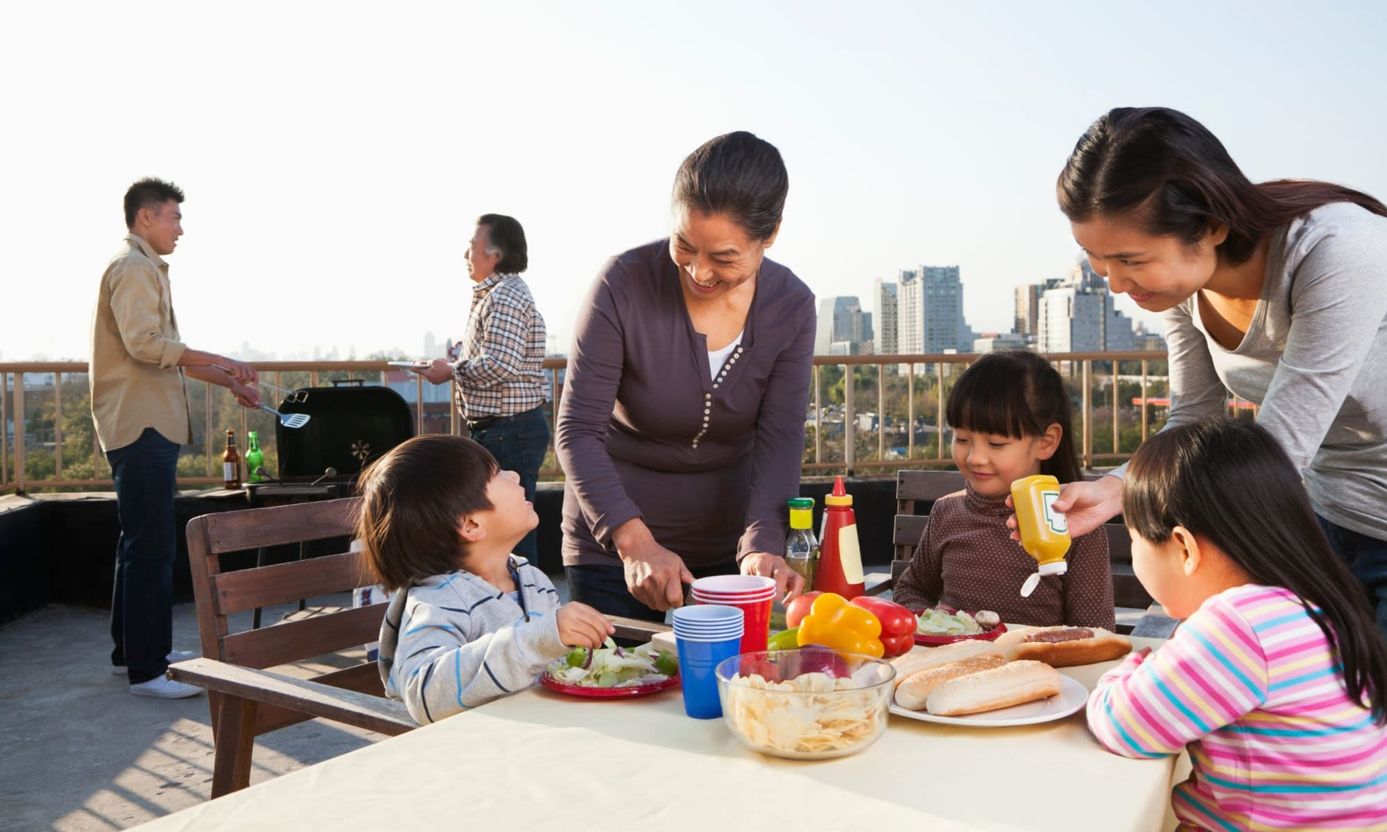 Family grilling and barbequing on a rooftop at Liberty SKY in Salt Lake City, Utah
