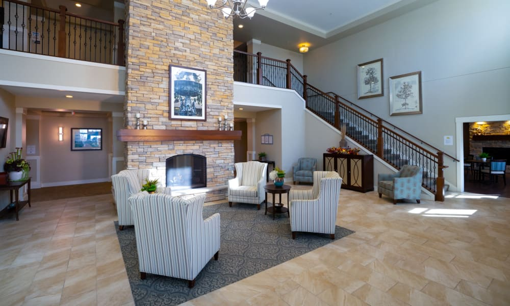 Modern foyer with cozy chairs and a stone fireplace at The Sanctuary at St. Cloud in St. Cloud, Minnesota