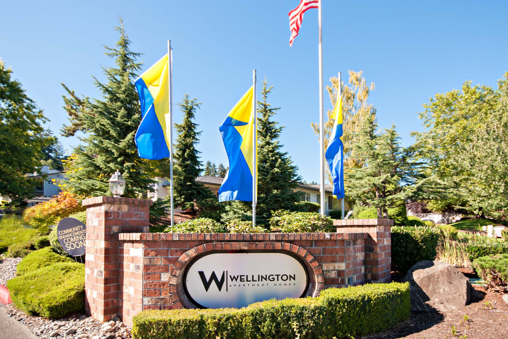The monument sign and flags at the entrance of Wellington Apartment Homes in Silverdale, Washington