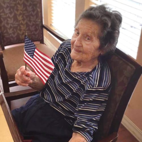 Lovely resident holding an american flag at Oxford Glen Memory Care at Grand Prairie in Grand Prairie, Texas