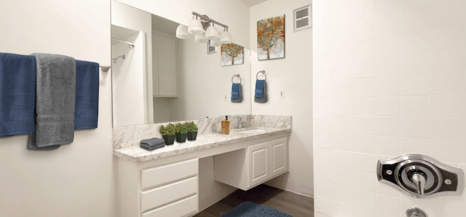 Well-lit bathroom with a large vanity mirror in a model classic apartment at Sunset Barrington Gardens in Los Angeles, California