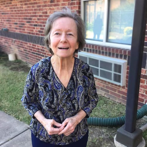 Resident standing outside smiling at Canoe Brook Assisted Living & Memory Care in Catoosa, Oklahoma