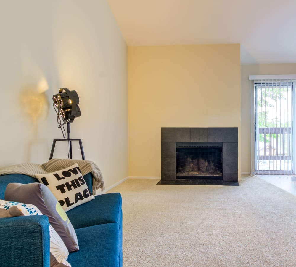Model home's living area with plush carpeting and a fireplace at Sofi Lake Oswego in Lake Oswego, Oregon