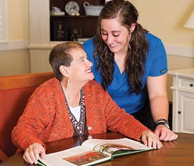 Resident and caregiver at Burr Ridge Senior Living discussing a book
