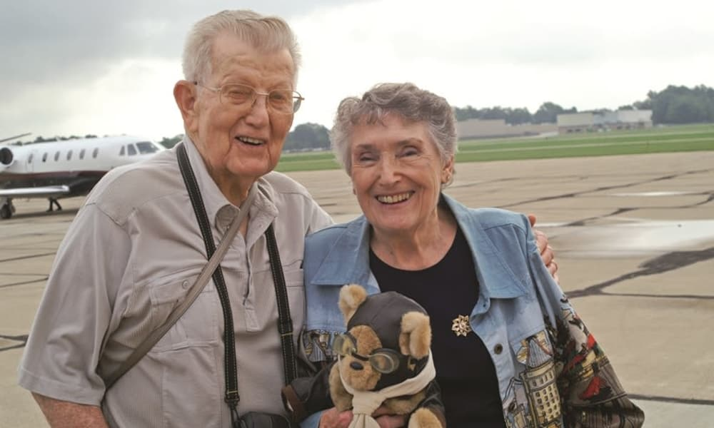An elderly couple from Carolina Estates in Greensboro, North Carolina in front of a plane
