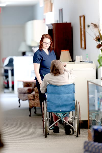 A staff member helping a resident in a wheelchair at Providence Assisted Living in Batesville, Mississippi.