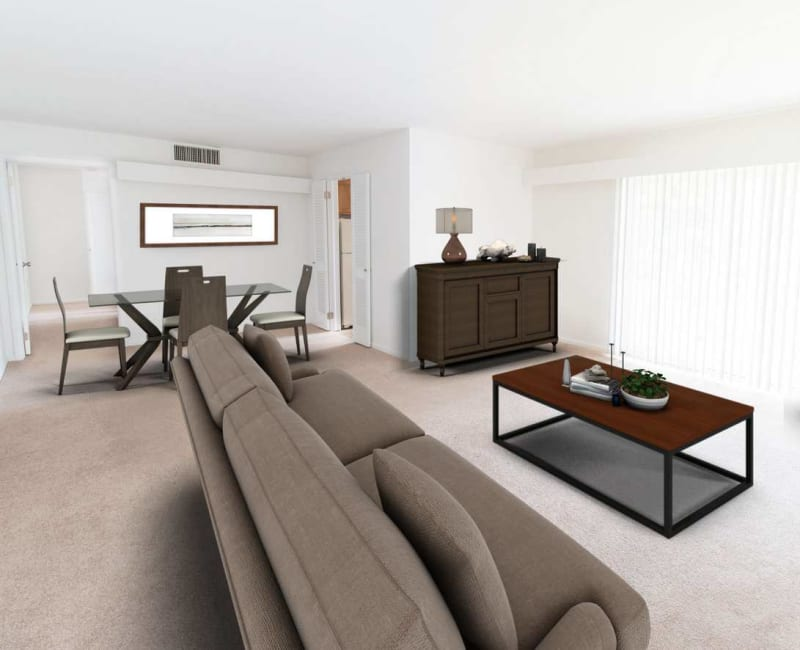 Open living room and dining area with wall-to-wall carpeting in a model home at Corliss Apartments in Phillipsburg, New Jersey