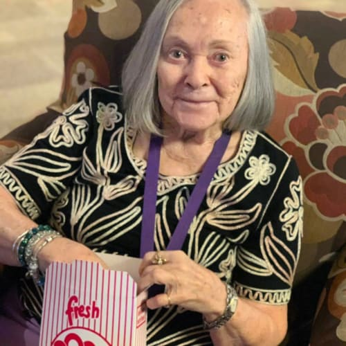 A happy resident eating popcorn at FountainBrook in Midwest City, Oklahoma