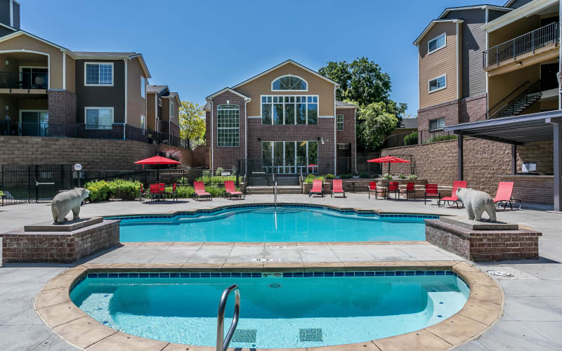 The spa and pool with lounge chairs and umbrellas at The Crossings at Bear Creek Apartments in Lakewood, Colorado