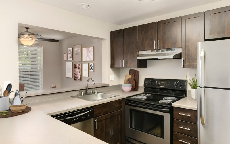 Fully equipped kitchen with brown cabinetry at Meadows at Cascade Park Apartments in Vancouver, Washington