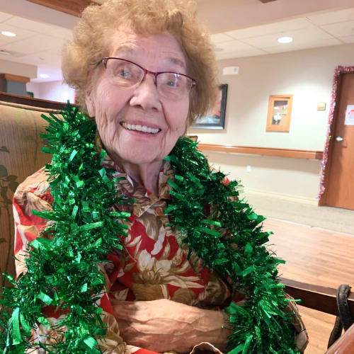 resident wearing a festive wreath at The Oxford Grand Assisted Living & Memory Care in Wichita, Kansas