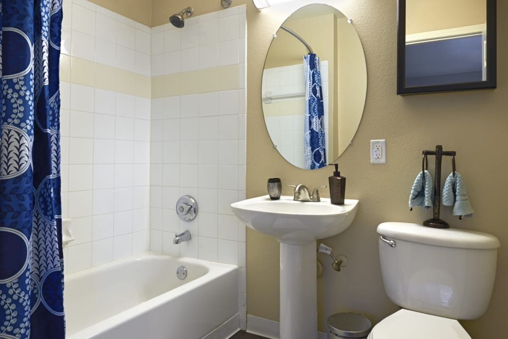 Bathroom with pedestal sink at Crossroads at City Center Apartments in Aurora, Colorado