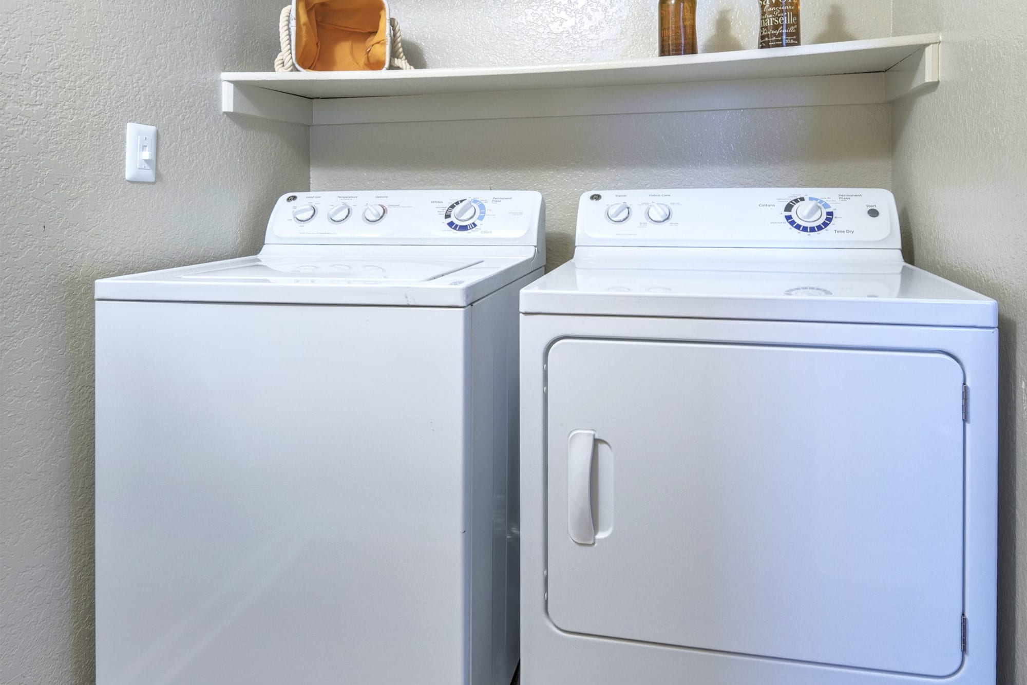 Full sized side by side washer and dryer at Arapahoe Club Apartments in Denver, Colorado
