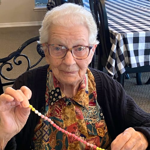 Resident holding a bead necklace at Canoe Brook Assisted Living in Ardmore, Oklahoma