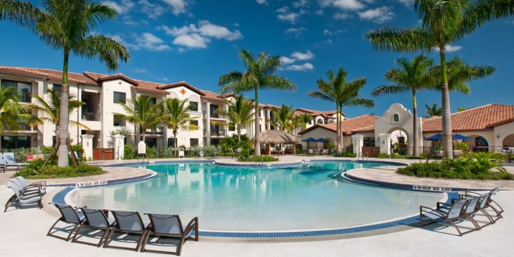 Swimming pool area with chaise lounge chairs on the sun deck at Doral View Apartments in Miami, Florida