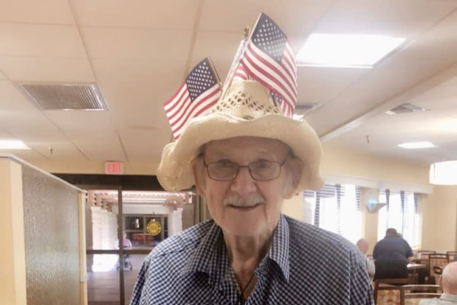 Resident posing for Flag Day with flags in his cap at Bella Vista Senior Living in Mesa, Arizona