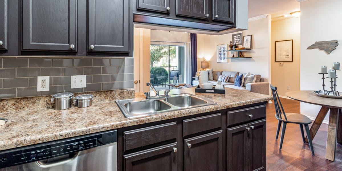 Modern style kitchen area with wood cabinets and flooring at Marquis of Carmel Valley in Charlotte, North Carolina