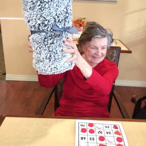Resident holding a prize at a bingo game at Oxford Glen Memory Care at Grand Prairie in Grand Prairie, Texas