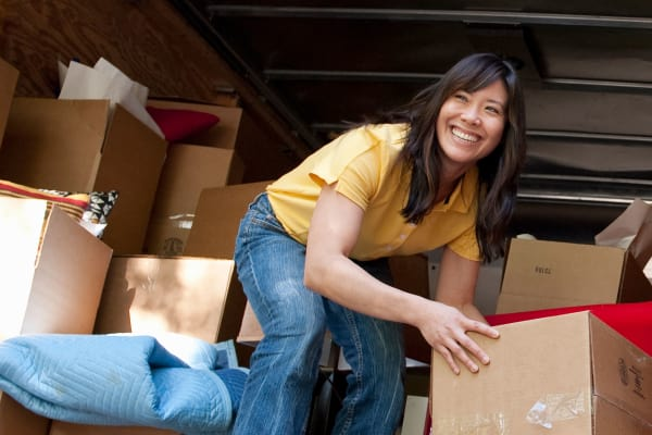 Happy lady unloading moving boxes at A Better Self Storage West in Colorado Springs, Colorado