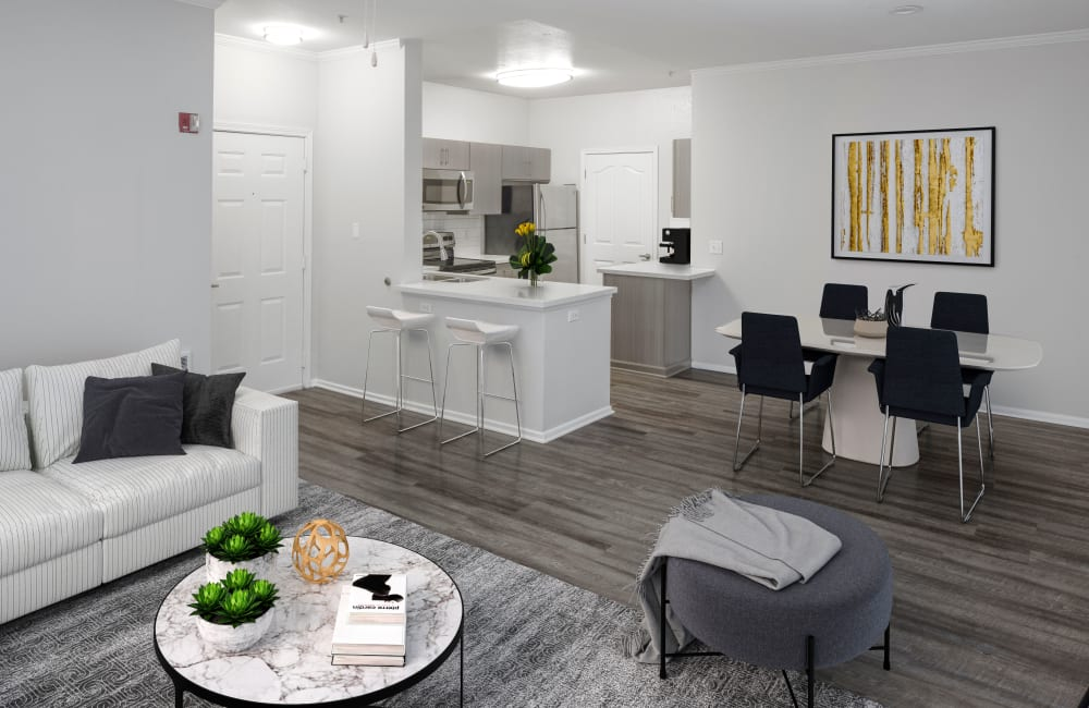 A fully furnished unit with a rug on top of hardwood floors, a couch, love seat and coffee table at The Grove at Orenco Station in Hillsboro, Oregon