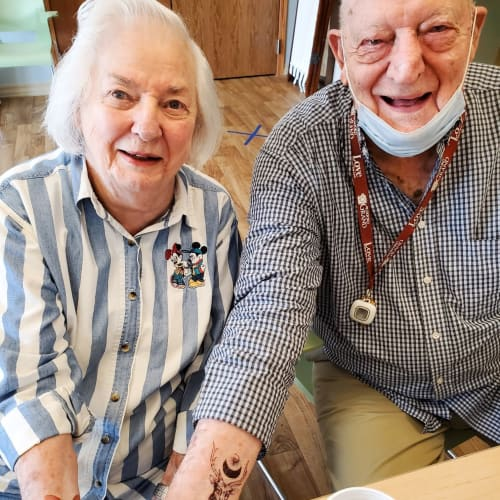 Resident couple showing off temporary tattoos at The Oxford Grand Assisted Living & Memory Care in Wichita, Kansas