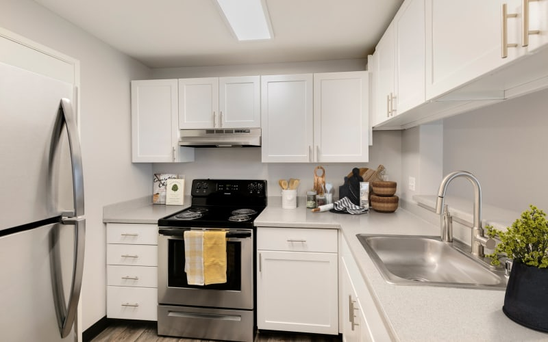Renovated kitchen with white cabinets at Meadows at Cascade Park Apartments in Vancouver, Washington