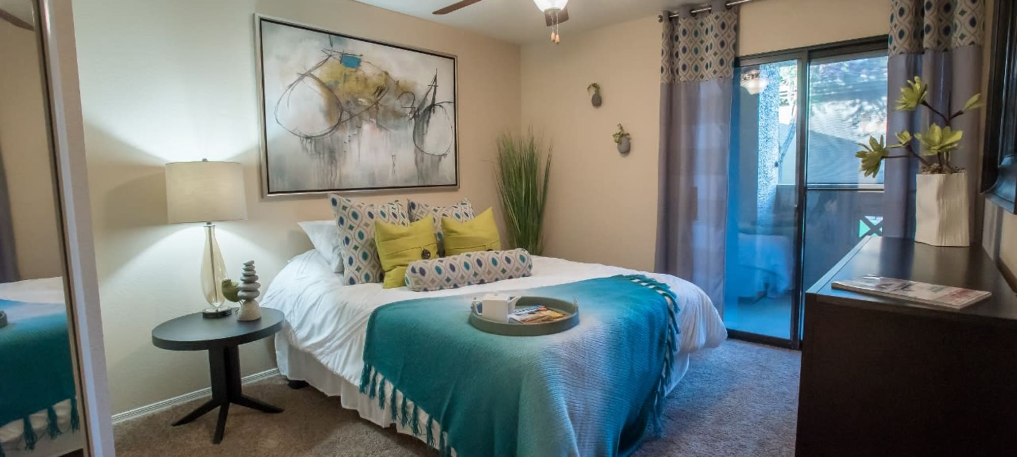 Bedroom with blue accents at The Palms on Scottsdale in Tempe, Arizona