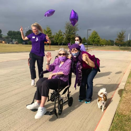 Group of caretakers escorting a resident and her dog at The Oxford Grand Assisted Living & Memory Care in McKinney, Texas