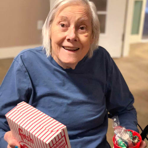 Smiling resident with popcorn and candy at FountainBrook in Midwest City, Oklahoma