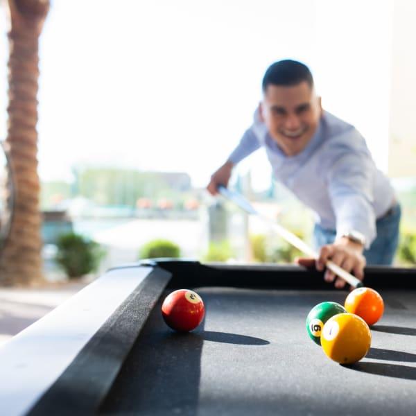 Resident enjoying pool table at BB Living at Val Vista in Gilbert, Arizona