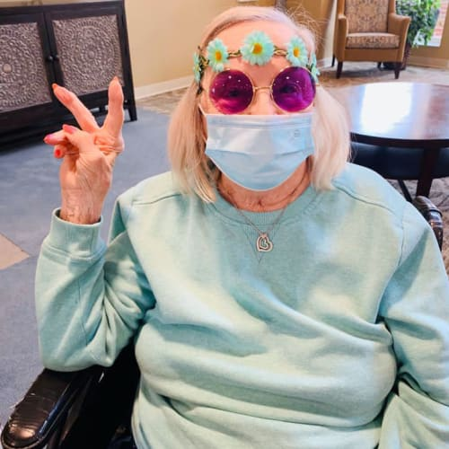 Resident in round purple glasses throwing up a 'peace' sign at The Oxford Grand Assisted Living & Memory Care in McKinney, Texas