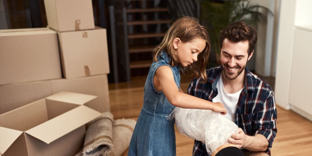Father and daughter wrap a lamp in bubble wrap, before storing it at Missouri Flat Storage Depot in Placerville, California