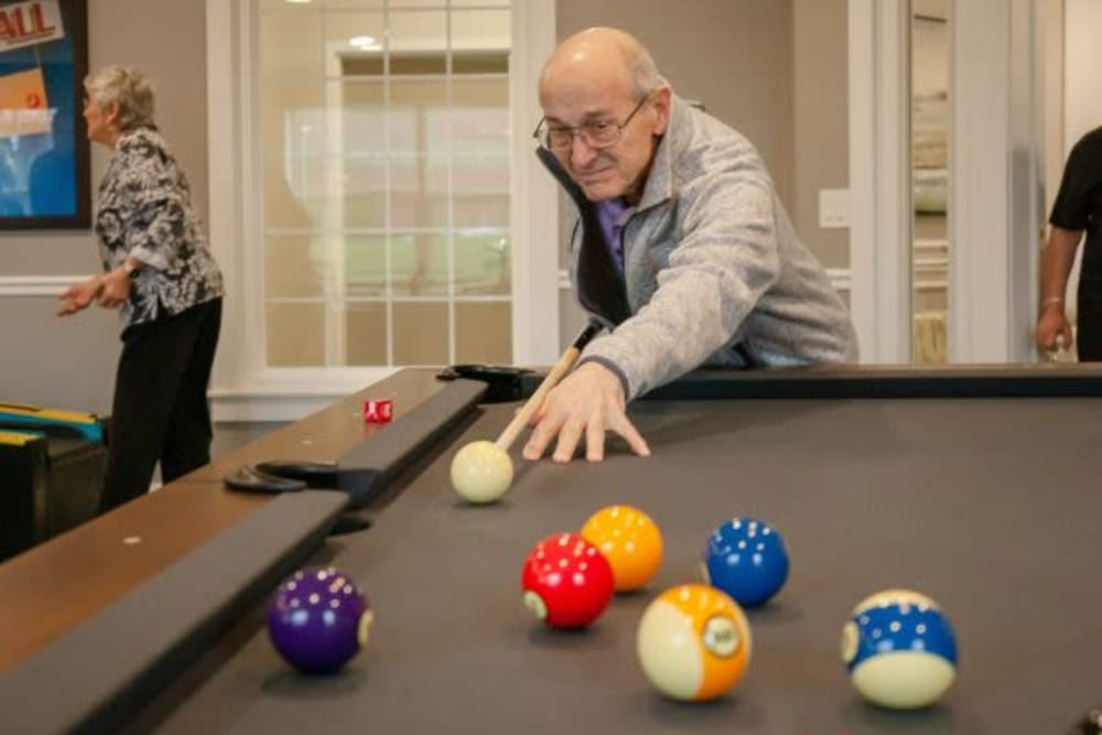 A resident playing a game of pool at Mercer Hill at Doylestown in Doylestown, Pennsylvania
