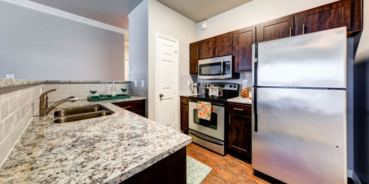 Modern style kitchen with granite counters and tile backsplash at Marquis at Silver Oaks in Grapevine, Texas