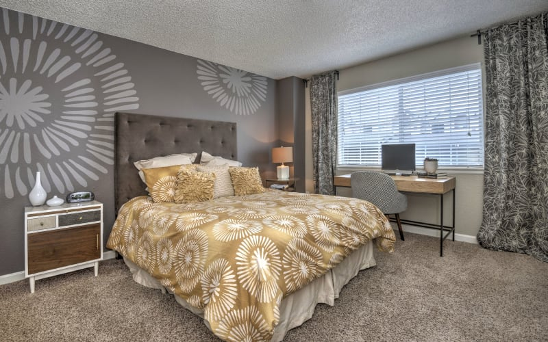 Spacious master bedroom with plush carpeting at Arapahoe Club Apartments in Denver, Colorado