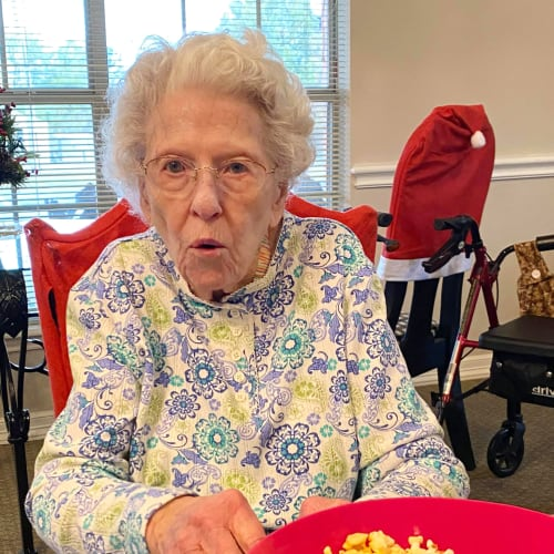 A resident sitting with a bowl of popcorn at Canoe Brook Assisted Living in Ardmore, Oklahoma