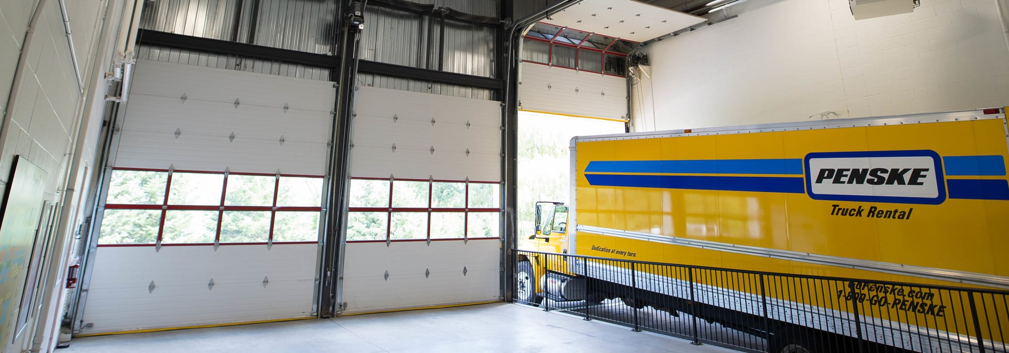Large loading bay with a rental truck inside at Apple Self Storage - Kitchener - Highland in Kitchener, Ontario