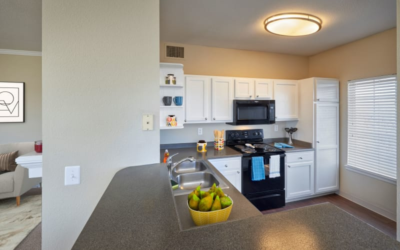 Renovated kitchen with white cabinets at Skyecrest Apartments in Lakewood, Colorado