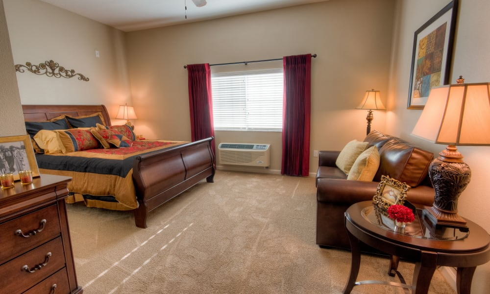 Spacious resident bedroom with carpeting at Inspired Living at Lakewood Ranch in Bradenton, Florida