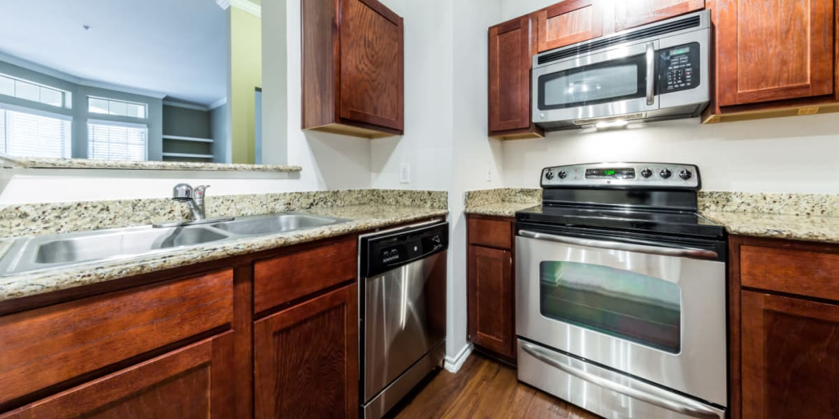 Modern kitchen with stainless steel appliances and granite counters at Marquis at Barton Trails in Austin, Texas