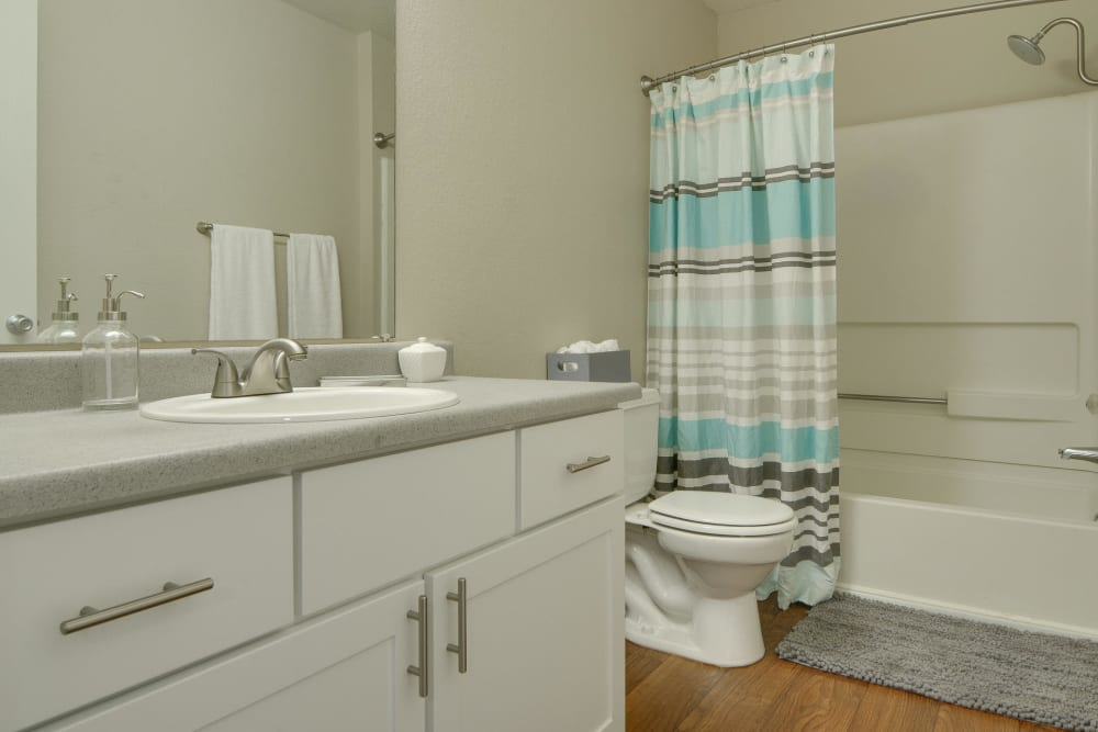 Bathroom with white cabinets and a tub at Carriage House Apartments in Vancouver, Washington