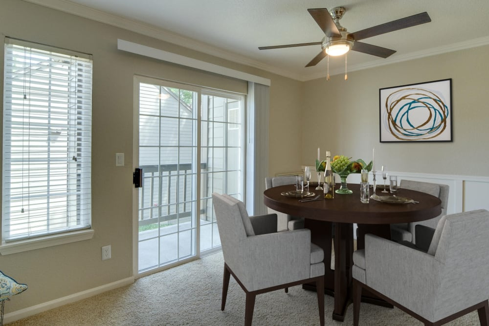 Dining room with a ceiling fan by patio doors at Carriage House Apartments in Vancouver, Washington