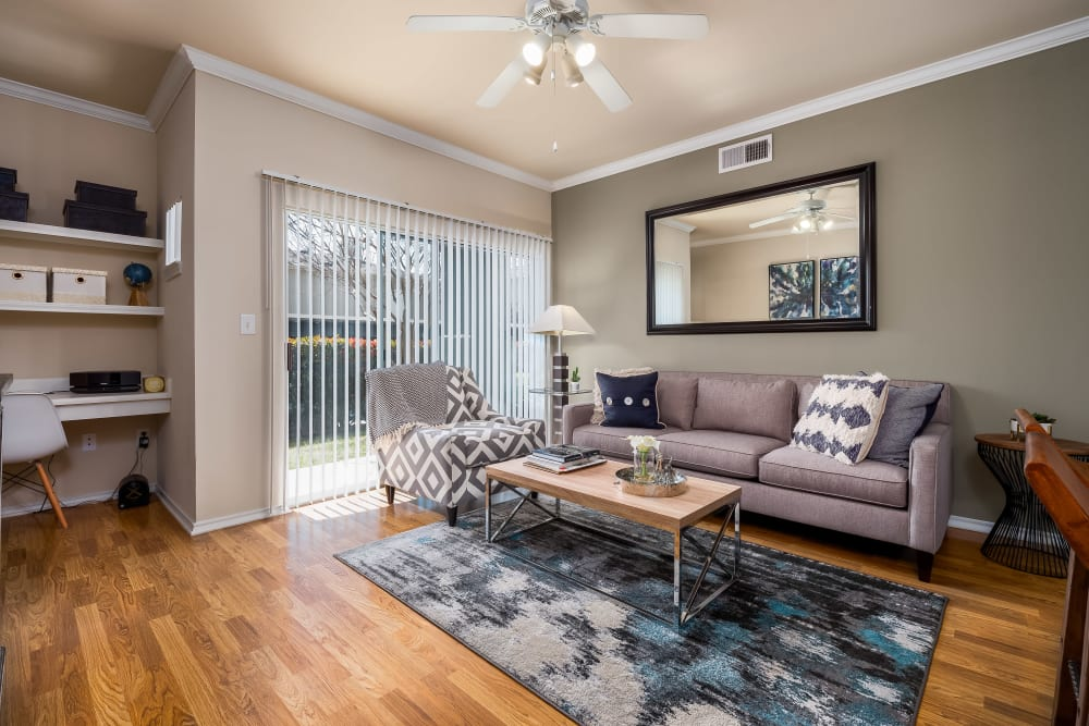 Living room with modern decor and patio access at Vail Quarters in Dallas, Texas