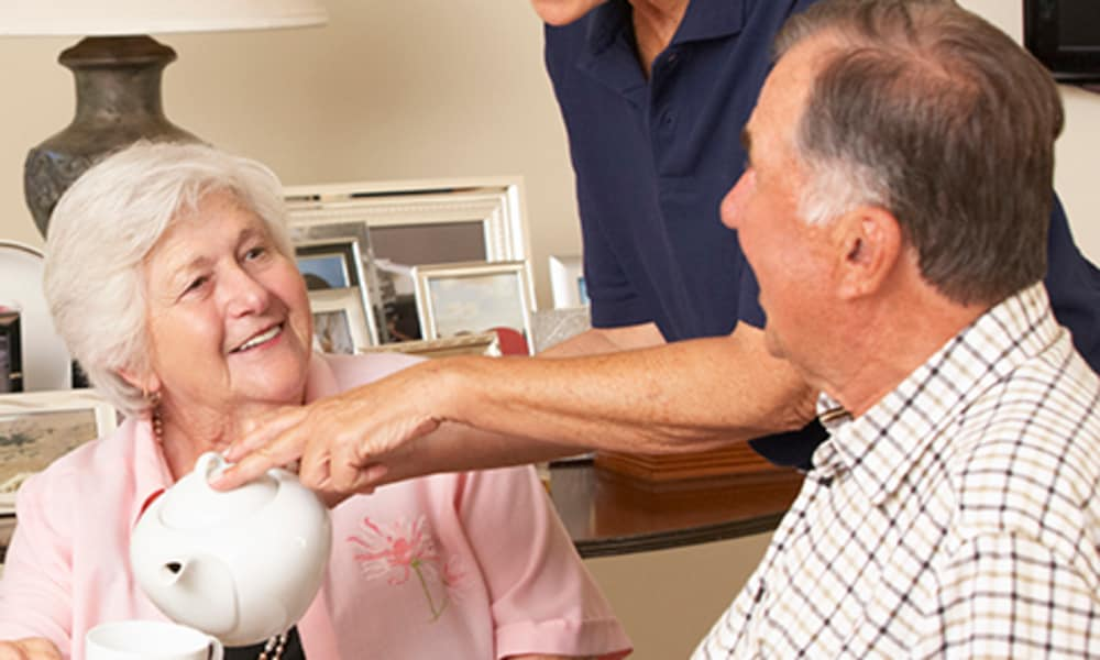 A resident talking to a caretaker at one of Americare Senior Living's locations