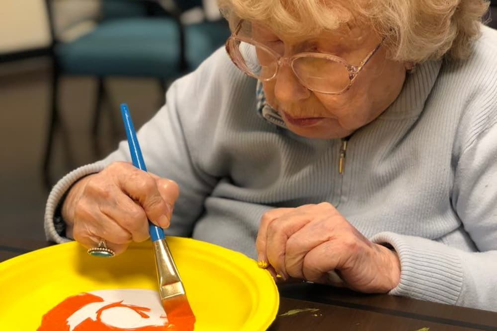 A resident painting a plate at Aspen Place Health Campus in Greensburg, Indiana