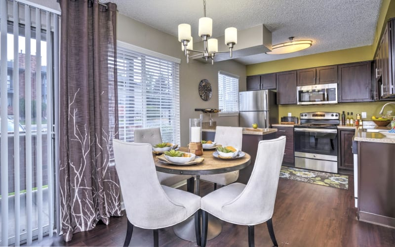 Dining room and renovated kitchen with stainless-steel appliances and espresso cabinets at Arapahoe Club Apartments in Denver, Colorado