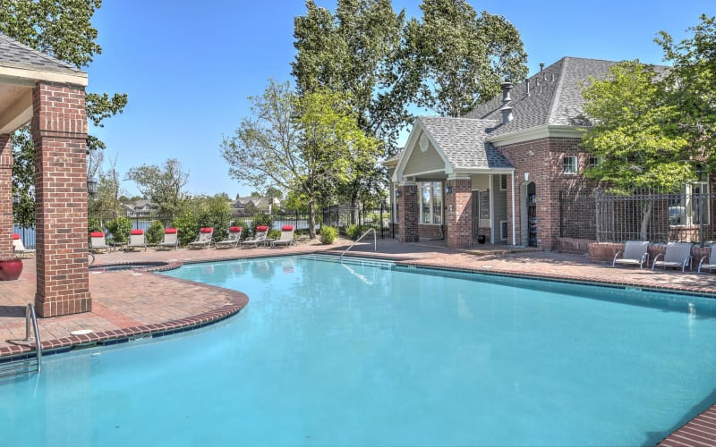 Large curved blue swimming pool at Promenade at Hunter's Glen Apartments in Thornton, Colorado