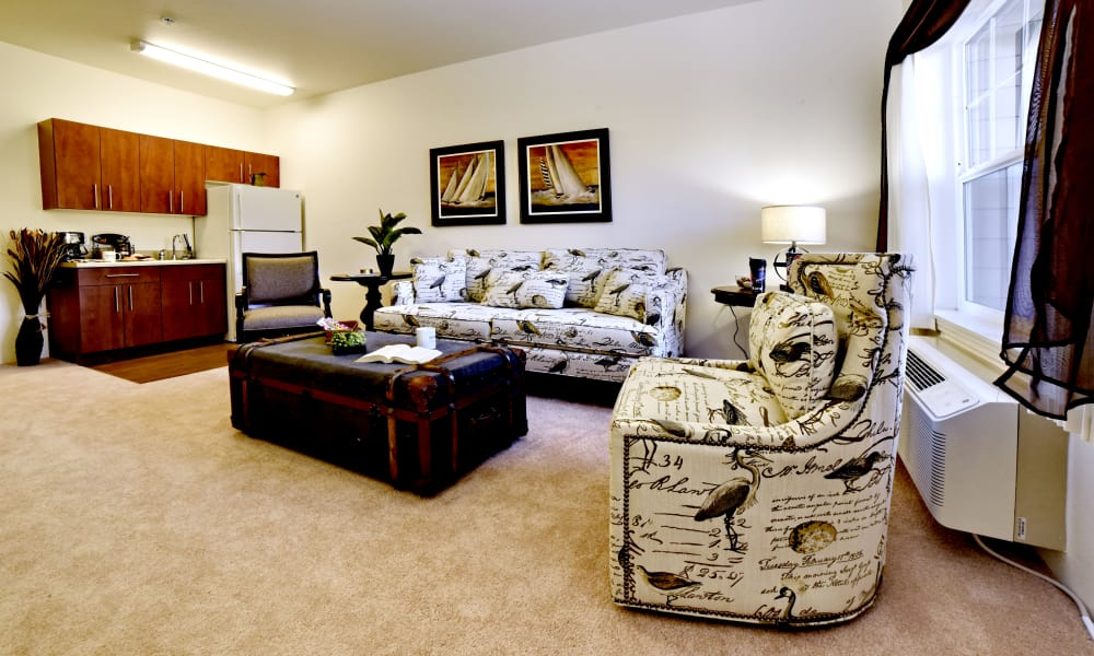 Cozy living room and open kitchen in an apartment at Maple Ridge Gracious Retirement Living in Cedar Park, Texas