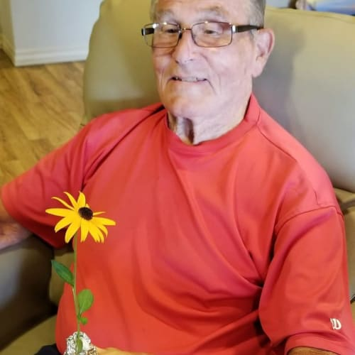 Resident holding a flower at The Oxford Grand Assisted Living & Memory Care in Wichita, Kansas